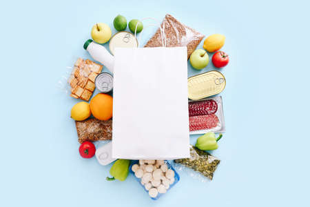 Food supplies for the period of quarantine on blue background. Set of grocery items from canned food, vegetables, cereal. Food delivery concept. Donation concept. Top view.