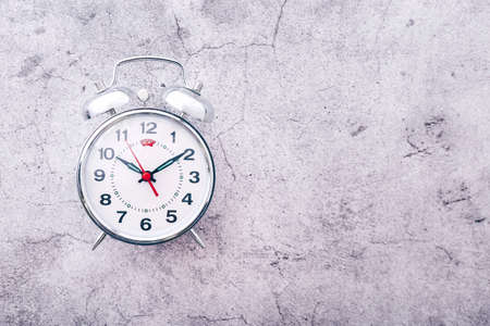 Silver alarm clock on cement background. Top view. Copy space