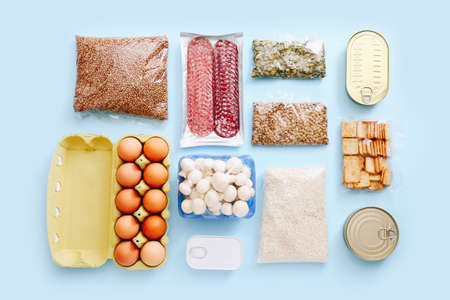 Set of grocery items from canned food, vegetables, cereal on blue background. Food delivery concept. Donation concept. Top view.