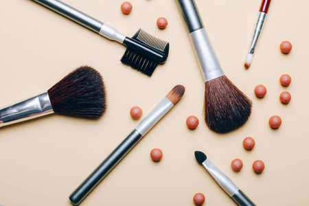 Set of makeup brushes with blush balls scattered on beige background. Cosmetic Product. Top view