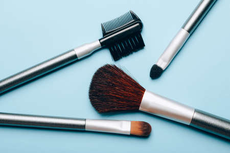 Set of makeup brushes scattered on blue background. Top view point, flat lay.