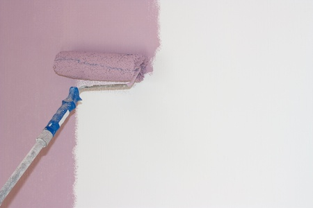 A roller with a pink color on the white wall  Stock Photo - 13358297