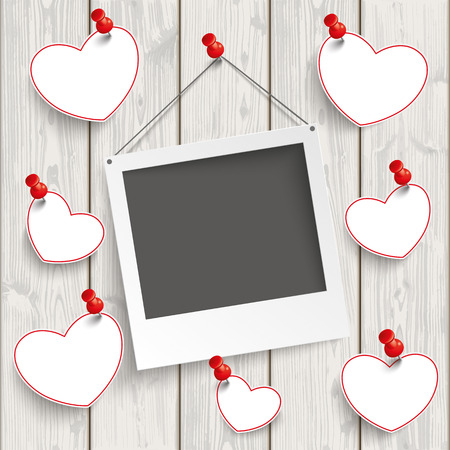 Instant photo frame with hanging hearts on the wooden background.