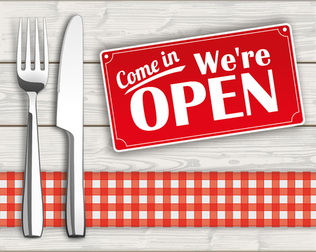 shop opening hours: Knife and fork with checked table cloth and sign on the wooden background.