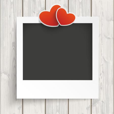 Instant-Bilderrahmen mit zwei Herzen auf dem hölzernen Hintergrund.