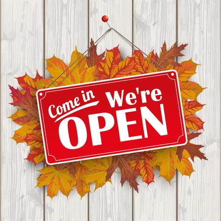 """Gebladerte van de herfst, met rode hangende teken en de tekst """"kom binnen, we zijn open""""."""