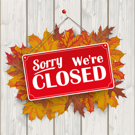 closing time: Autumn foliage with red hanging sign and text sorry, were closed.