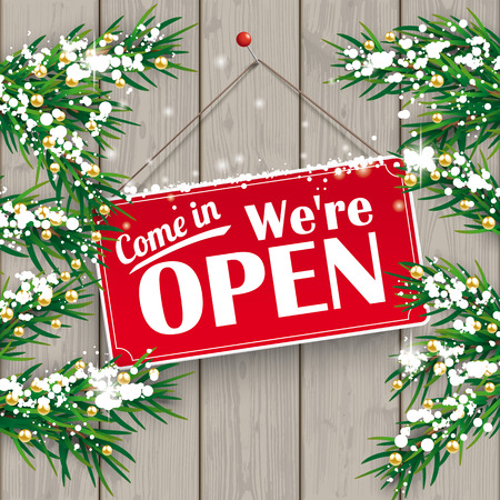 Christmas fir twigs with We are open sign and snow on the wooden background.