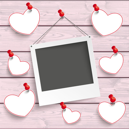 Instant photo frame with hanging hearts on the pink wooden background. Eps 10 vector file.