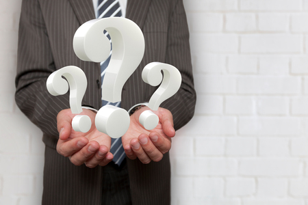 photomanipulation: Businessman hands with 3 question marks.