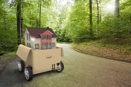 House building in the moving box with wheels on the road in the forest. 3d illustration with photo composing.