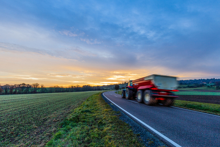 Tractor on the road in the morning. Stock Photo