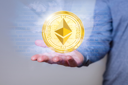 Golden ethereum coin with fog and bits in the human hand.