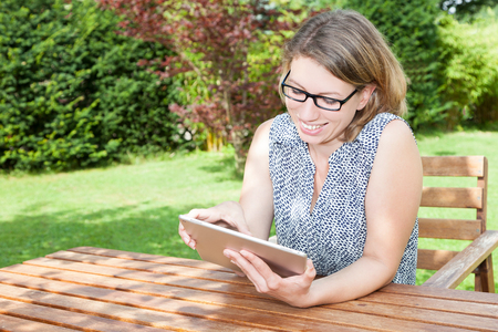 Smiling woman sitting with tablet pc in the garden.