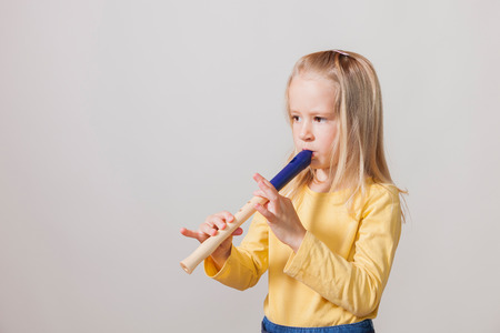Blond hair girl with flute on the bright background.