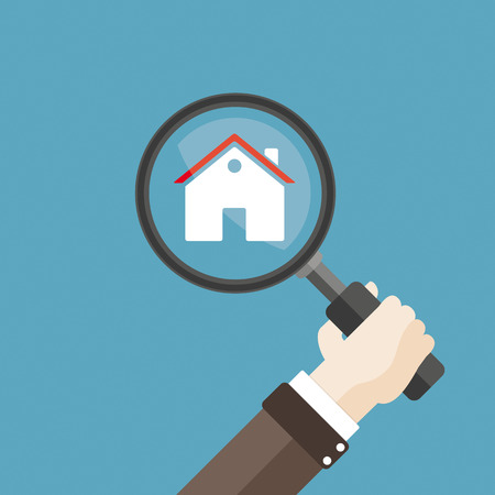 Human hand with magnifying glass and a house