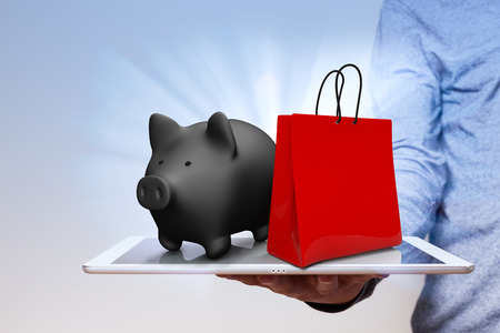 Man with tablet pc, shopping bag and piggy bank.