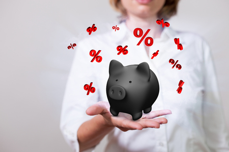 Woman with black piggy bank and red percents.