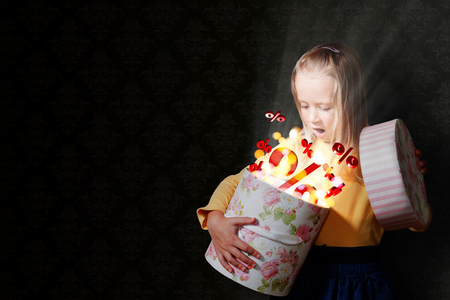 Blond haarmeisje met geopende giftdoos en rode percents.