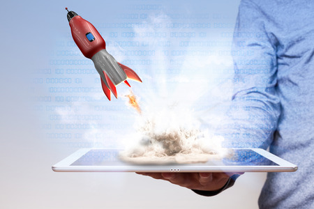 Mans hand with tablet pc and starting digital rocket.  Stock Photo