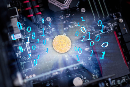 Golden bitcoin on the motherboard with bytes.