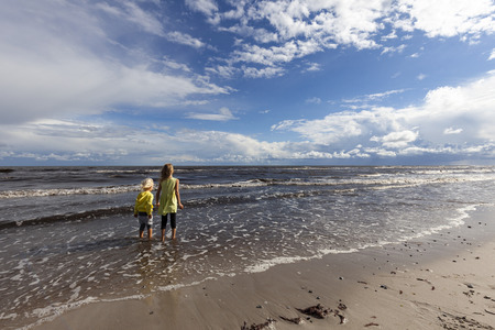 Siblings stand on the shore of a windy sea.
