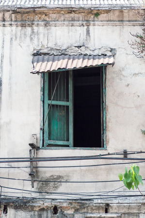 an awning: An old green wooden window with tin awning on an old house Stock Photo