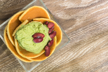 enrich: green tea icecream enrich with pancake in glass cup on wooden backgroud
