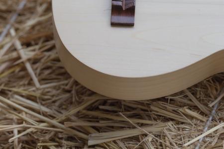 fingering: a part of light tone ukulele on straw stack background