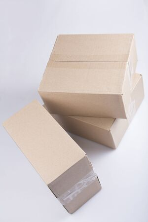 isolated close up shot of three stacked closed rectangular blank brown carton cardboard boxes on a white background