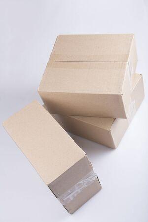 Gros plan isolé de trois boîtes en carton carton brun vierge rectangulaires empilées sur un fond blanc
