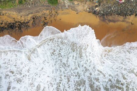 aerial drone bird view shot of the sea shore with yellow sand, black rocks, large white waves and foam crashing on the beach forming beautiful textures, patterns, shapes. Sri Lanka