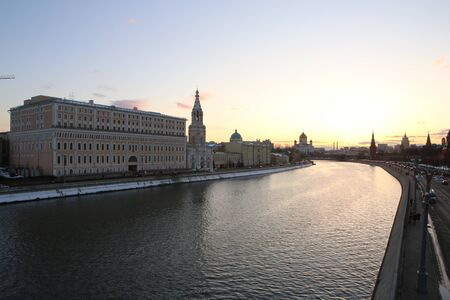 panorama cityscape shot of Moscow river, Saint Sophia Church, Christ the Saviour Cathedral and the walls of Kremlin monument. Taken in Moscow, Russia from a bridge during bright yellow sunset.