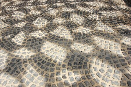 filled frame background wallpaper of a black, grey and white sett paving surface forming beautiful geometrical shapes and patterns