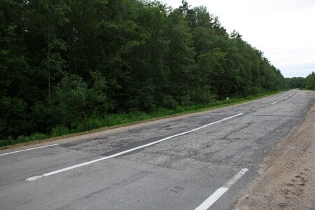 sudden harsh difference and contrast between a good and bad weathered damaged road at Vladimir Okrug border.
