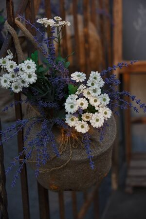 vertical close up macro shot of fake plastic white daisy and blue purple lavender flowers arrangement in a sack basket pot hanging on a railing in front of a house. Archivio Fotografico