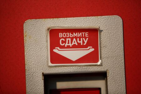 A filled frame close up macro shot of an old red vending coin machine and a sticker with white text that says in Cyrillic Russian TAKE YOUR CASH Imagens