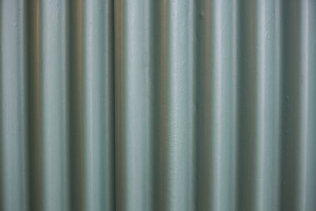 filled frame close up background wallpaper shot of a galvanized green metal sheet wall with vertical lines and black shadows