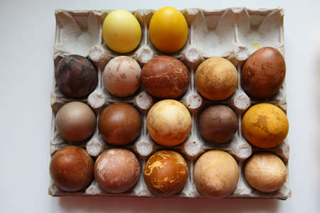 top view shot of a box of seventeen original, unique colorful dragon or dinosaur looking like chicken Easter eggs, dyed with natural products (red wine, tea, coffee, carrots, turmeric, soy sauce)