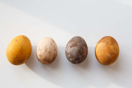 a row of four original, unique colorful dragon or dinosaur looking like chicken Easter eggs, dyed with natural products (red wine, tea, coffee, carrots, turmeric, soy sauce) on a white background 免版税图像