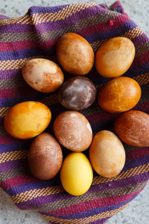 vertical shot of a bunch of original colorful dragon or dinosaur looking like chicken Easter eggs, dyed with natural products (red wine, tea, coffee, carrots, turmeric) in a bowl on a purple towel 免版税图像