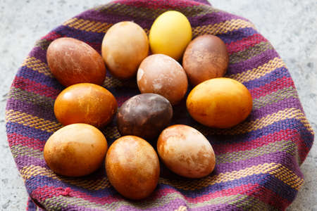 bunch of original colorful dragon or dinosaur looking like chicken Easter eggs, dyed with natural products (red wine, tea, coffee, carrots, turmeric) in a bowl on a purple towel