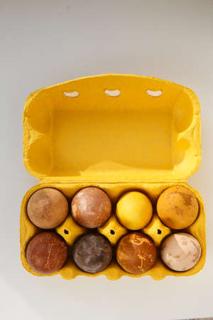 vertical shot of a yellow box with eight original, unique colorful dragon or dinosaur looking like chicken Easter eggs, dyed with natural products (red wine, tea, coffee, carrots, turmeric, soy sauce)