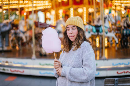 Young girl with a cotton candy at a Christmas fair wearing a yellow wool cap and a gray wool sweater.