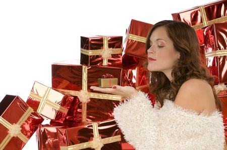 Beautiful lady watching a tiny present in front of pile of gifts Stock Photo - 3787844