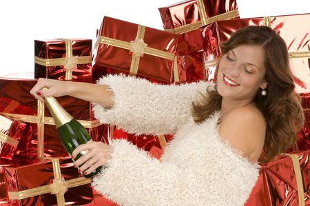 Beautiful lady opening a bottle with champagne in front of pile of gifts Stock Photo - 3787846