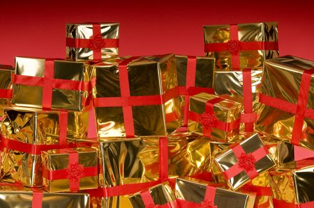 Pile of Christmas presents wrapped in gold foil on red background Stock Photo - 3792069