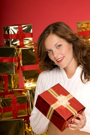 Beautiful brunette offering a Christmas gift in front of pile of gifts Stock Photo - 3794930