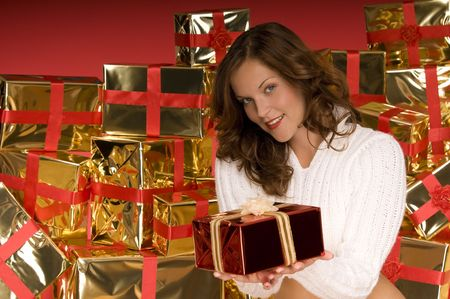 Beautiful brunette offering a Christmas gift in front of pile of gifts Stock Photo - 3794935