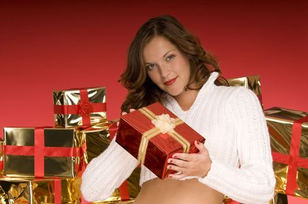 Beautiful model giving a Christmas present in front of pile of gifts and red background Stock Photo - 3794924